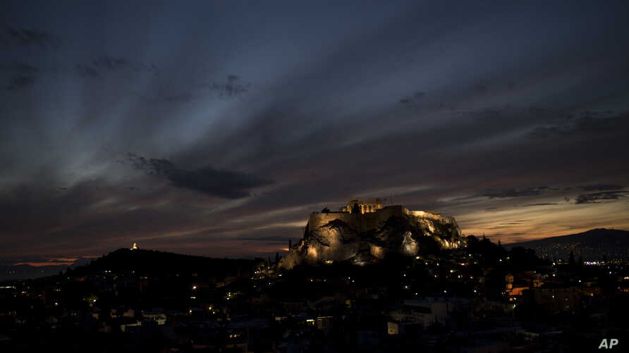 The sun sets behind the ancient Acropolis hill and the ruins of the fifth century B.C. Parthenon temple in Athens, on Thursday, Nov. 9, 2017.