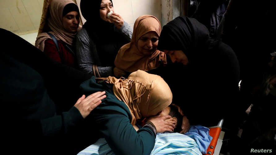 The mother of Palestinian Mosab al-Tamimi, who was killed during clashes with Israeli troops, kisses his body at a hospital in the West Bank city of Ramallah Jan. 3, 2018.