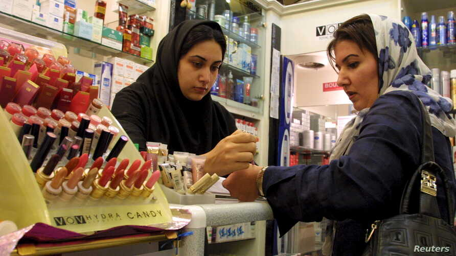 An Iranian woman tests the colours of make-up at an upscale shop in north Tehran, Nov. 8, 2003.