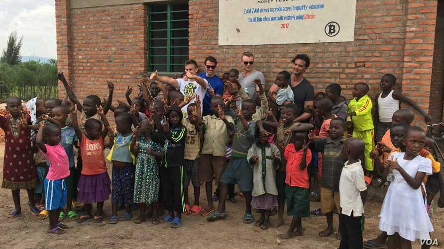 A new preschool, constructed with #BuiltWithBitcoin fundraising, brings new opportunities to youngsters in the Rwandan village of Kasebigege. Paxful CEO Ray Youssef, holding a child and not wearing sunglasses, led fundraising. (Courtesy photo)