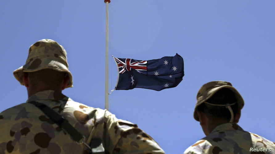 FILE - Australian troops stand at attention during a ceremony at Camp Armadillo in Afghanistan's in Helmand province, April 25, 2008.
