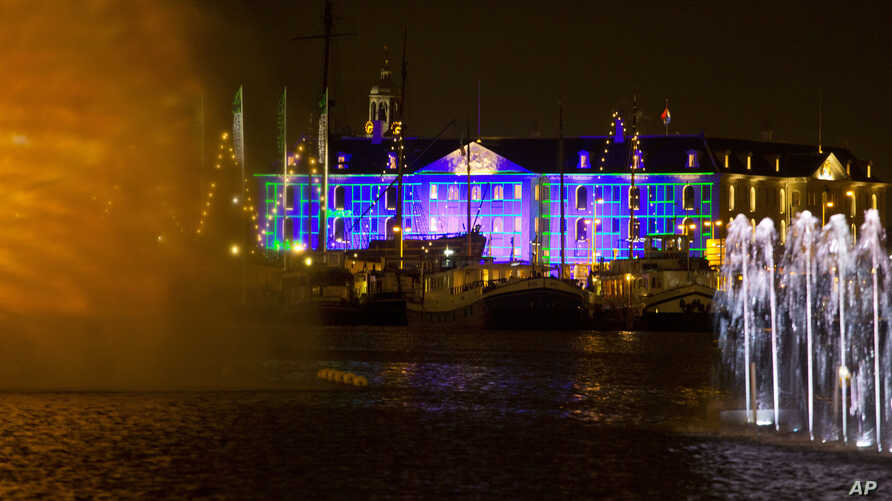 Blue Print by Dutch light designer Reier Pos is seen projected on the Nautical Museum, rear, as Arco, an art work by Austrian artist Teresa Mar is seen in the foreground, both installations are part of the Amsterdam Light Festival, Netherlands, Wedne