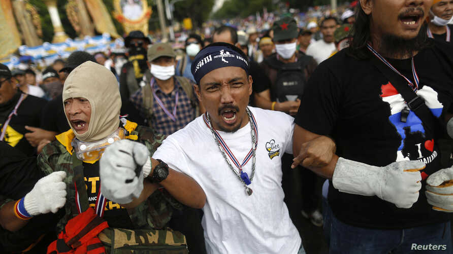 Anti-government protesters shout as they get ready to attack a police barricade near the Government house in Bangkok, Nov. 25, 2013.