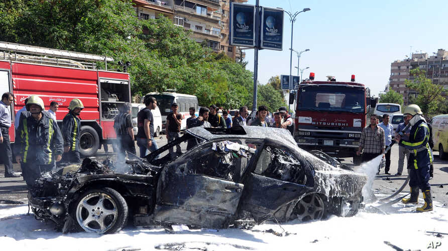 This photo released by the Syrian official news agency SANA, shows Syrian fire fighters extinguishing burning cars after a car bomb exploded in the capital's western neighborhood of Mazzeh, in Damascus, Syria, April. 29, 2013.