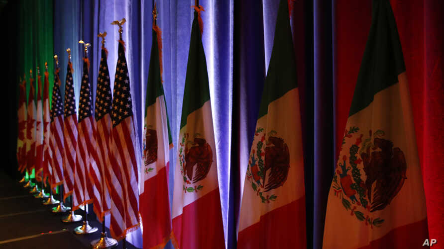 The flags of Canada, the U.S. and Mexico are lit by stage lights before a news conference at the start of NAFTA renegotiations in Washington, Aug. 16, 2017.