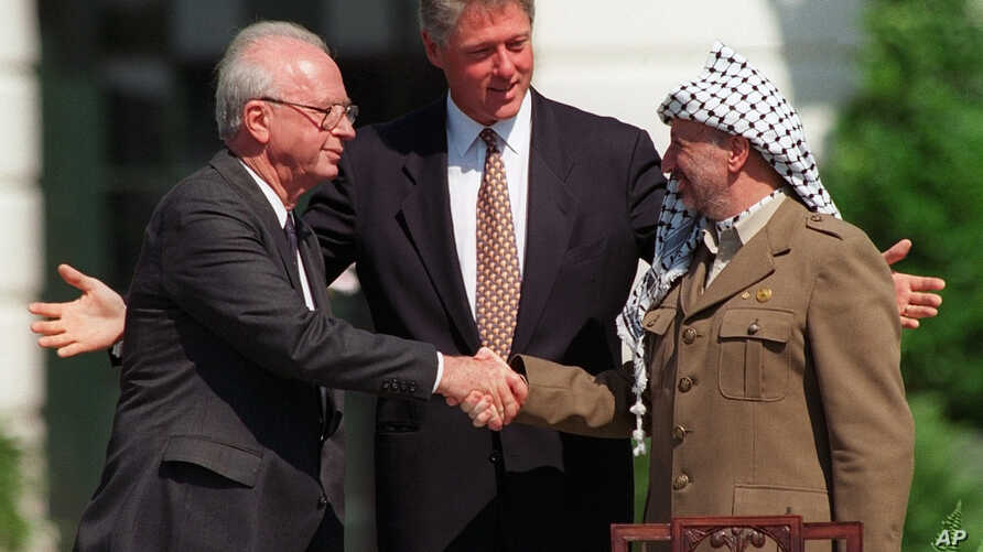 FILE - Israeli Prime Minister Yitzhak Rabin, left, and PLO chairman Yasser Arafat, right, shake hands as President Bill Clinton presides over the ceremony marking the signing of the 1993 peace accord between Israel and the Palestinians on the White H