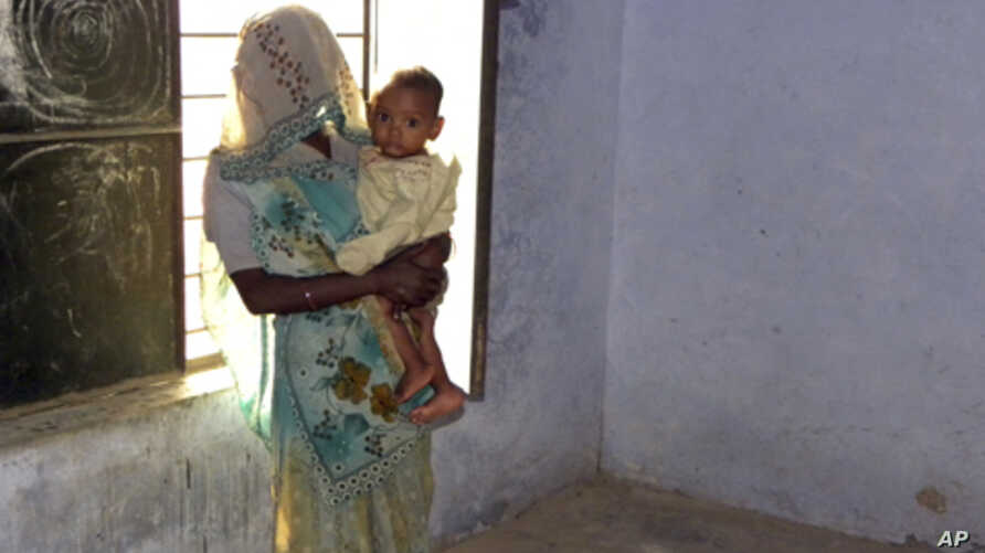 Phul Kumari, 25, stands with her child in a village community center in Baghpat district, in India's northern state of Uttar Pradesh October 18, 2011. Kumari  was trafficked to Uttar Pradesh as a bride for her husband and has been repeatedly raped by
