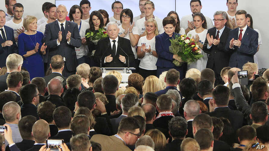 Conservative Law and Justice leader Jaroslaw Kaczynski, center left, and Justice candidate for the Prime Minister Beata Szydlo, center right, react at the party's headquarters in Warsaw, Poland, on Sunday, Oct. 25, 2015.