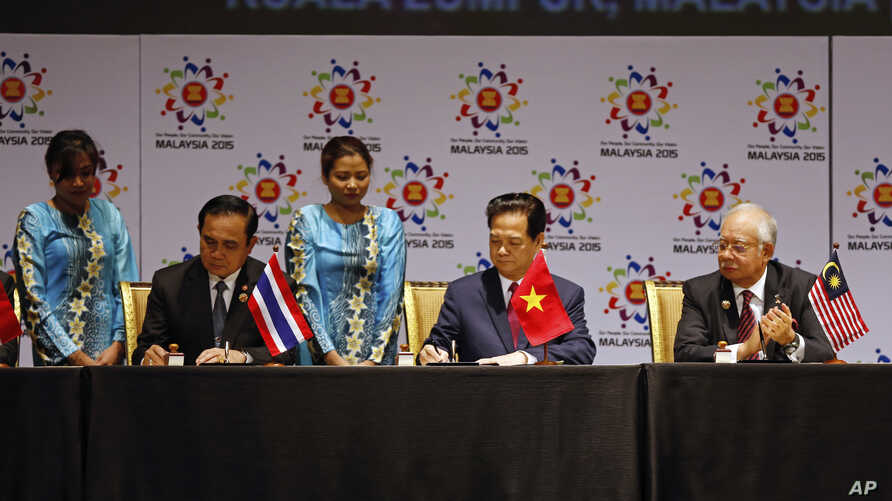 Thai Prime Minister Prayuth Chan-ocha, left, and Vietnam's Prime Minister Nguyen Tan Dung, center, sign documents as Malaysia's Prime Minister Najib Razak looks on during the signing ceremony of the 2015 Kuala Lumpur Declaration on the Establishment