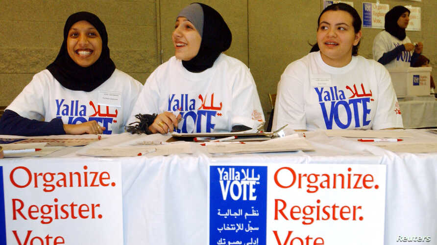 Farhana Quayoum (L), Angel Ouza (C) and Rhima Aoun volunteer at a rally encouraging Arab-Americans to register and vote during this Saturday's democratic presidential caucus, in Dearborn, Michigan February 4, 2004. Arab-Americans across the country h