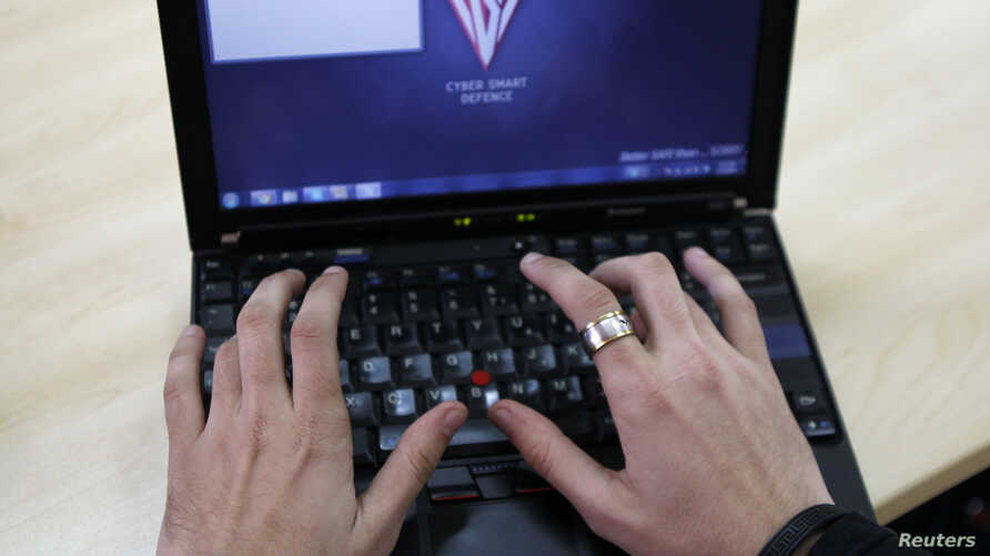 Romanian Razvan Cernaianu, formerly known as a hacker by the name of TinKode, works at his laptop in his office in Bucharest in this March 15, 2013 file picture.