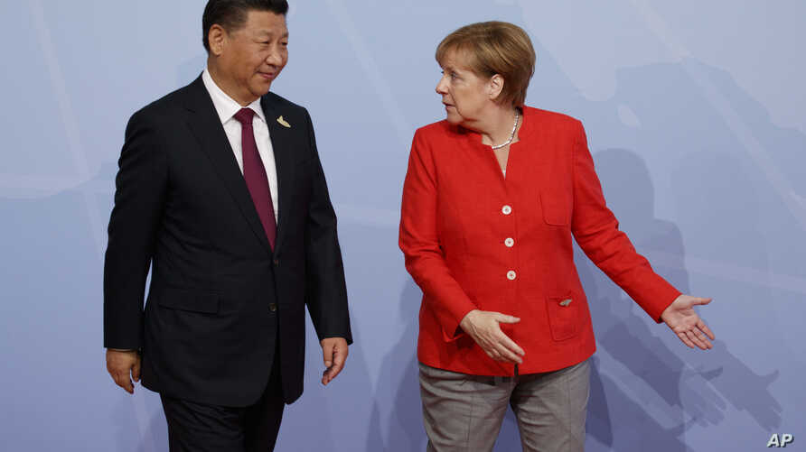 FILE - Chinese President Xi Jinping is greeted by German Chancellor Angela Merkel after arriving at the G-20 Summit, July 7, 2017, in Hamburg.