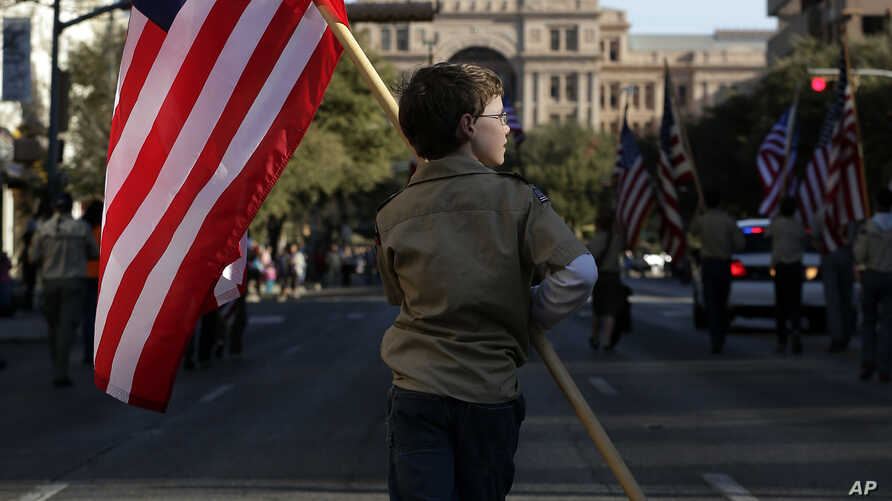 FILE - A Boy Scout carries a U.S. flag up Congress Avenue toward the Texas Capitol, Feb. 2, 2013.