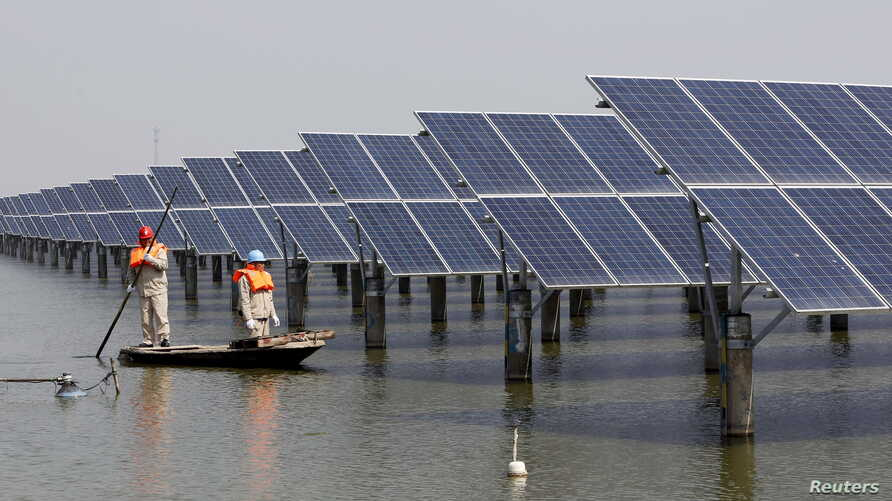 Employees row a boat as they examine solar panel boards at a pond in Lianyungang, Jiangsu Province, China, March 16, 2016.