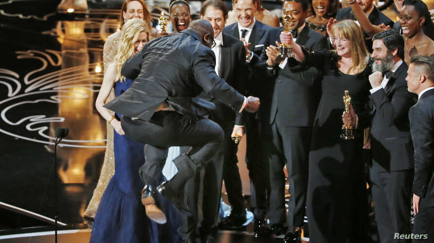 """Director and producer Steve McQueen jumps after accepting the Oscar for best picture for his work in """"12 Years a Slave"""" at the 86th Academy Awards in Hollywood, CA, March 2, 2014."""