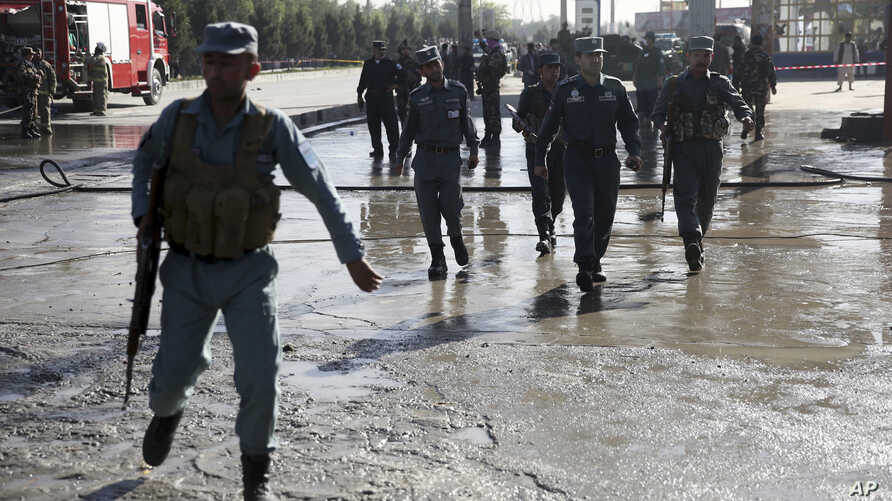 Afghan police soldiers inspect the site of a suicide attack in Kabul, Afghanistan, Monday, June 20, 2016.