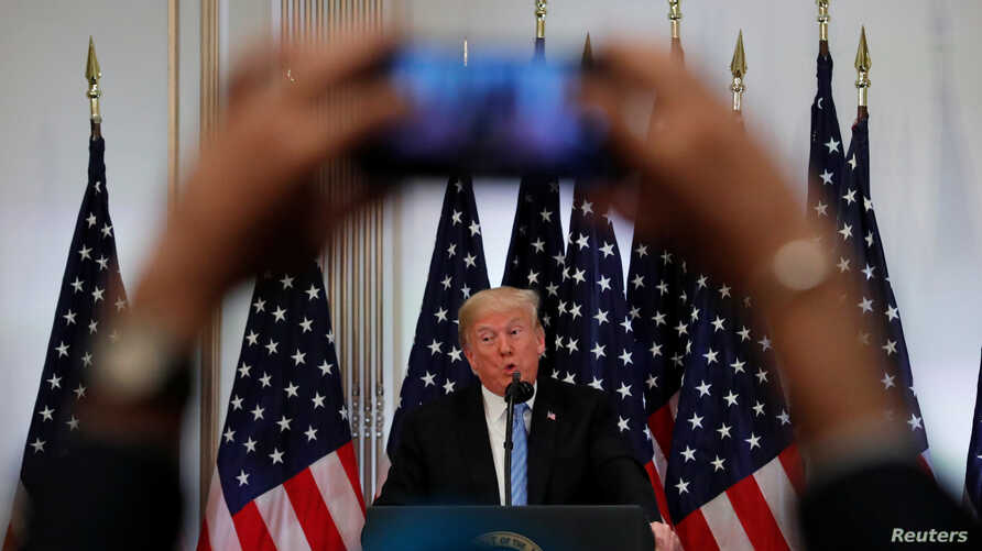 A reporter uses his mobile phone to record U.S. President Donald Trump at a news conference on the sidelines of the 73rd session of the United Nations General Assembly in New York, Sept. 26, 2018.