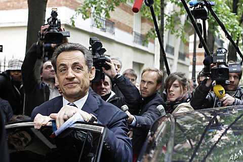 French President and UMP party candidate for the elections Nicolas Sarkozy, left, prepares to enter a car as he leaves his campaign headquarters the morning after the first round of voting in Paris, April 23, 2012.