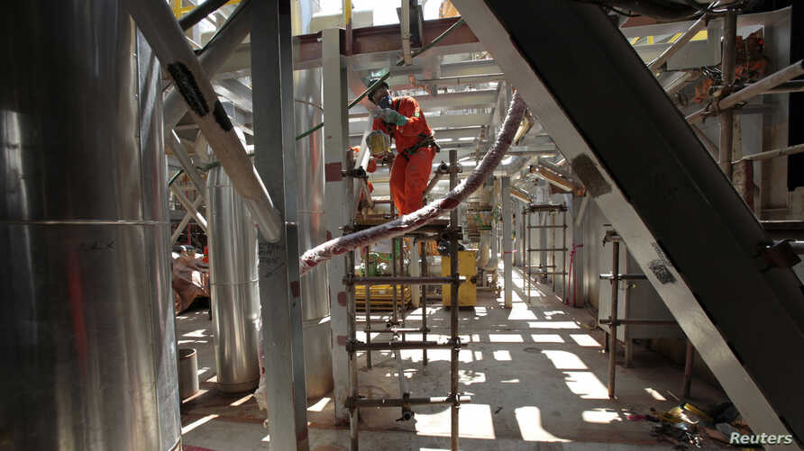 FILE - An employee works on the final stage of the construction of the new P-56 semi-submersible production platform for oil company Petrobras at the Brasfels shipyard in Angra dos Reis, about 185 kilometers (115 miles) west of Rio de Janeiro, Februa