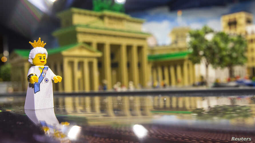 FILE - A Lego figure representing Britain's Queen Elizabeth II is placed in front of the Brandenburg Gate made of Lego bricks, in Legoland in Berlin, Germany, June 18, 2015. Lego has unveiled a new model in honor of the May 19 royal wedding of Prince