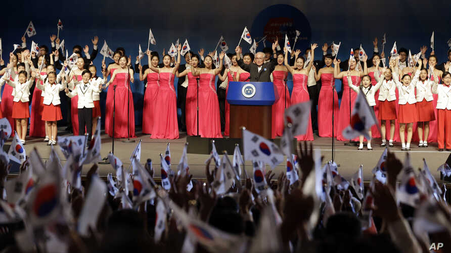 FILE - Participants give three cheers during a ceremony to mark the South Korean Liberation Day from Japanese colonial rule in 1945 in Seoul, South Korea, Aug. 15, 2013.