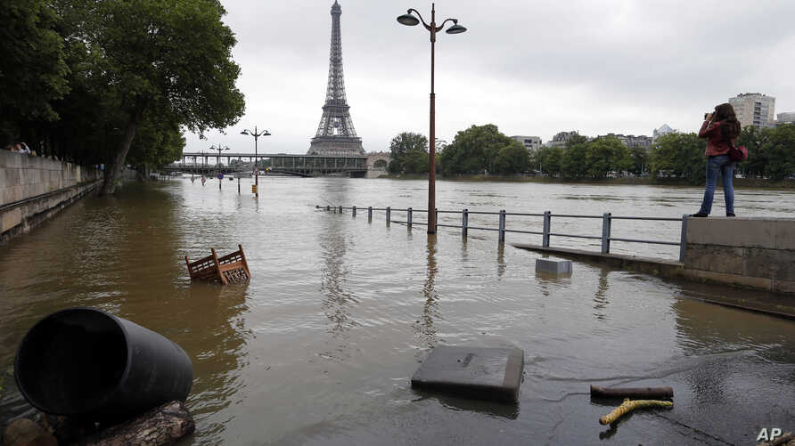 FILE - In this June 4, 2016, file photo, a woman, at right, takes photos of the flooded banks of the Seine in Paris. Scientists said at the time that man-made climate change had nearly doubled the likelihood of April 2016's devastating French floodin