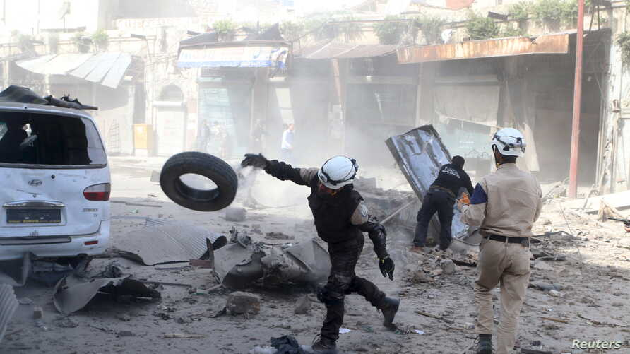 Civil defense members look for survivors after an airstrike on the rebel-held Old Aleppo, Syria, April 16, 2016.