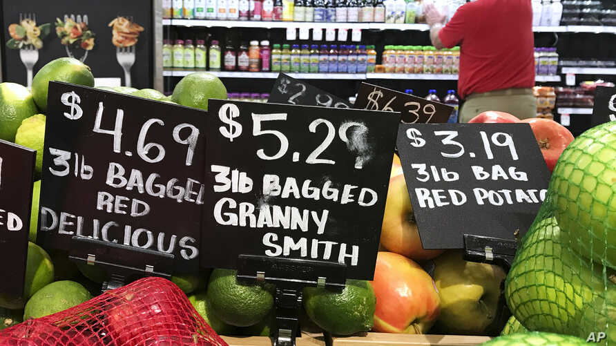 FILE - Price tags for delicious red, and granny smith apples and red potatoes are on display at a grocery store in Aventura, Fla., June14, 2018.