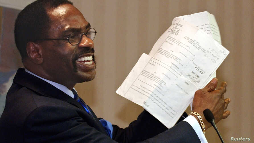 """FILE - In this Jan. 29, 2004, file photo, former boxer, Rubin """"Hurricane"""" Carter, holds up the document that freed him from prison, during a news conference held in Sacramento, California."""