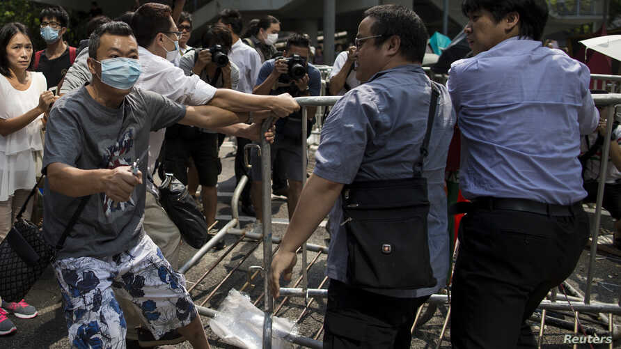 An anti-Occupy Central protester (L) holds pliers as he cuts cable ties at barricades setup as road blocks by protesters at Central in Hong Kong, October 13, 2014.