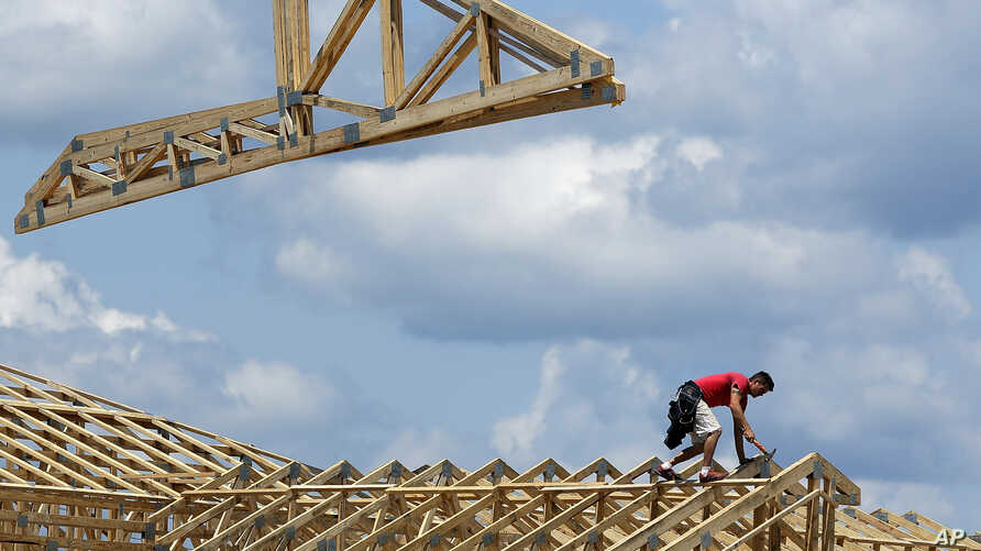 In this Thursday, July 17, 2014 photo construction workers build a commercial complex in Springfield, Illinois.