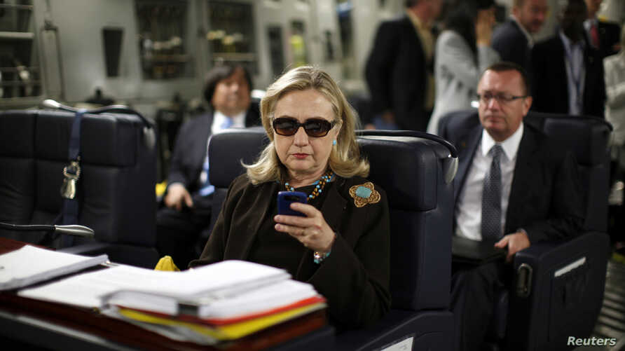 FILE - Then US secretary of state Hillary Clinton checks her mobile phone upon her departure in a military C-17 plane from Malta bound for Tripoli,  Libya, Oct. 18, 2011.