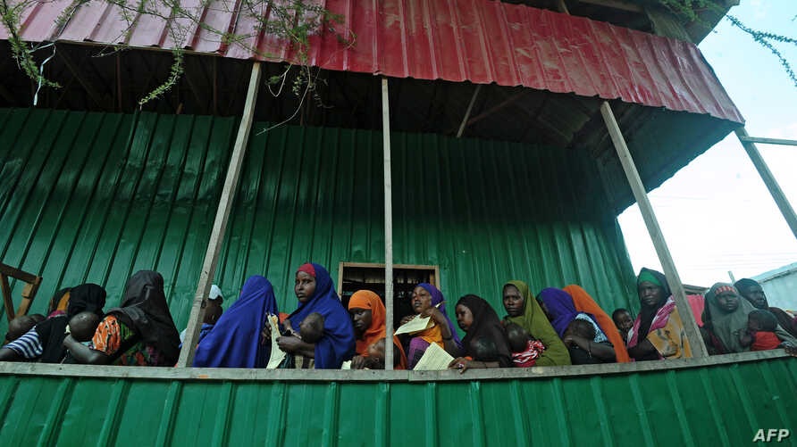 FILE - Newly displaced Somali women queue with their malnourished children as they try to receive medical treatment on outskirts of Mogadishu on April 11, 2017.