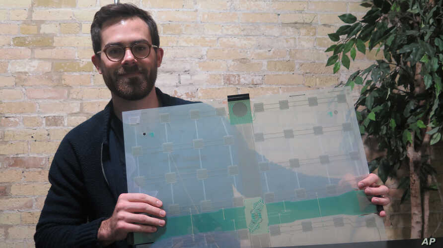 FILE - Scanalytics co-founder and CEO Joe Scanlin holds a smart-floor sensor his company creates that tracks people's movements, in Milwaukee, Wisconsin, Dec. 5, 2017.
