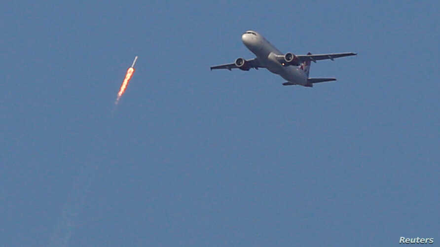 A recycled SpaceX Falcon 9 rocket soars toward space above a Virgin Airlines passenger jet, which had just departed Orlando International Airport, in Orlando, Florida, March 30, 2017. The launch marked the first time ever that a rocket was reused for