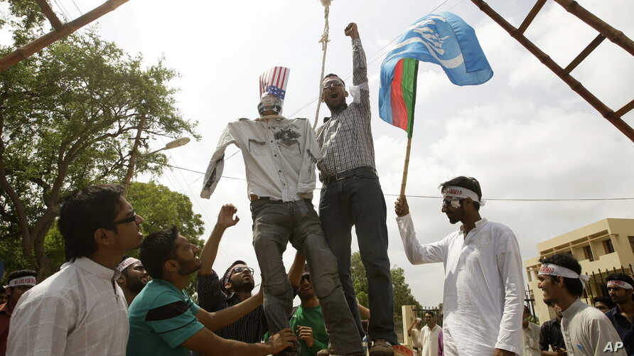 Pakistani students hang an effigy of US pastor Terry Jones at a rally to protest against the making of a film insulting the Prophet Muhammad at Karachi University in Pakistan, September 26, 2012.