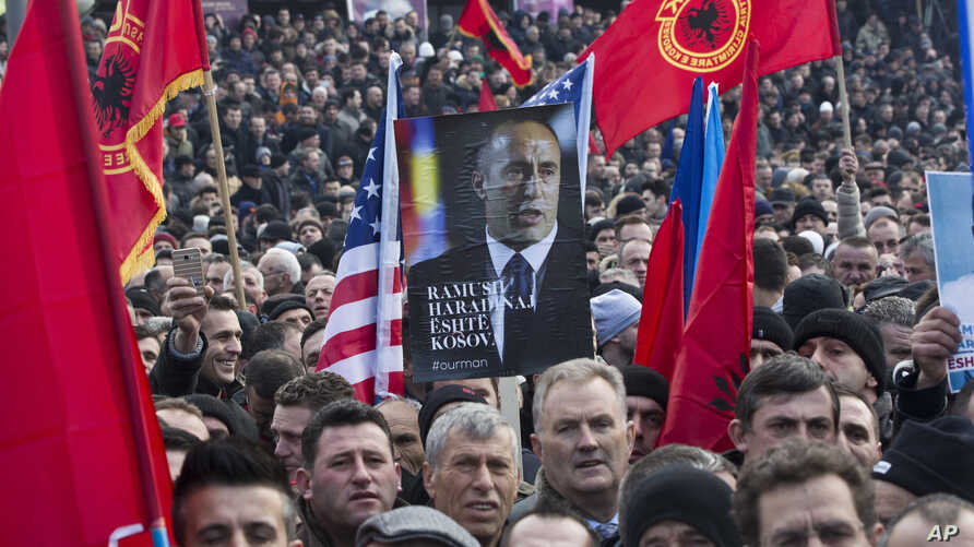 Thousands of protesters waving Albanian, Kosovan and U.S flags march during a protest demanding the immediate release from French judicial supervision of Ramush Haradinaj, Kosovo's former prime minister and a former guerrilla fighter, in Kosovo's cap