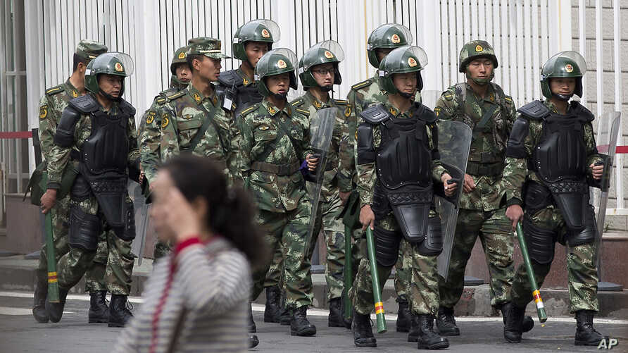 Paramilitary policemen with shields and batons patrol near the People's Square in Urumqi, China's northwestern region of Xinjiang,May 23, 2014.