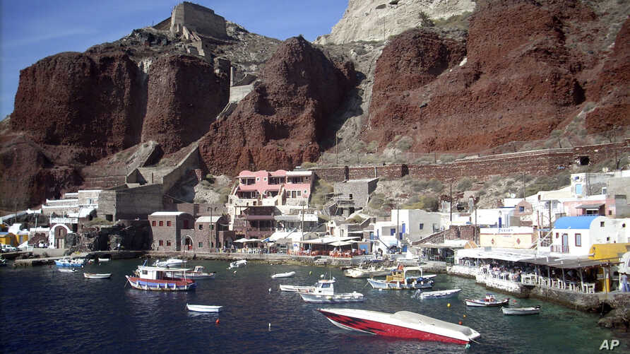 FILE  - In this Sept. 21, 2009 photo, boats are seen on Ammoudi Bay near seaside tavernas on the island of Santorini, Greece. Tax authorities say they have used surveillance drones in Greece for the first time to spot violations on Santorini, where t
