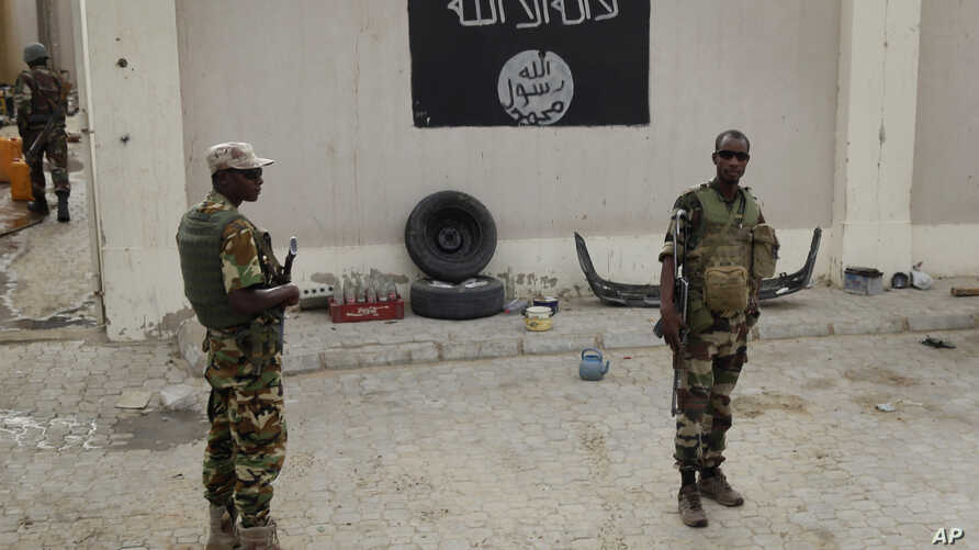 FILE - Soldiers stand at a checkpoint in front of a Boko Haram flag the Nigerian city of Damasak, Nigeria, March 18, 2015. The majority of suspects in a terrorism-related trial under way in Senegal are believed to have traveled to Nigeria and fought