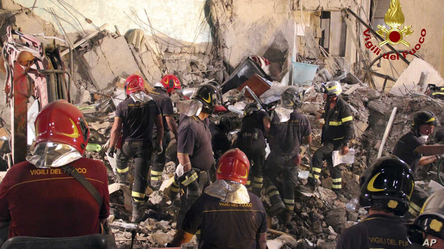 Firefighters search amid rubble of a collapsed apartment in Torre Annunziata, near Naples, Italy, July 8, 2017. Italian firefighters say eight bodies have been pulled from the rubble of a five-story apartment building that partially collapsed in a se