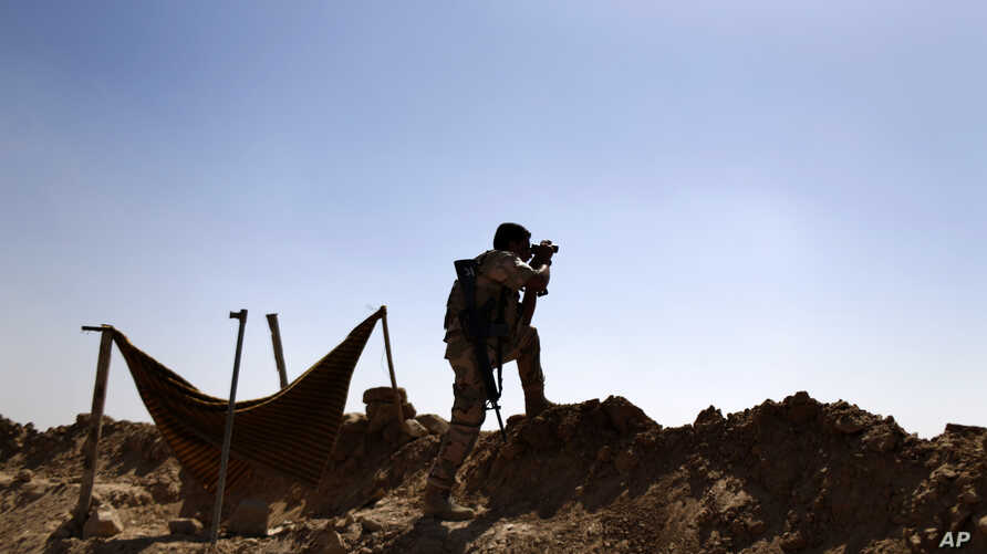 A Kurdish Peshmerga fighter uses binoculars to check on Islamic State group's positions on the outskirts of Makhmour, 300 kilometers (186 miles) north of Baghdad, Iraq, Sept. 6, 2014.