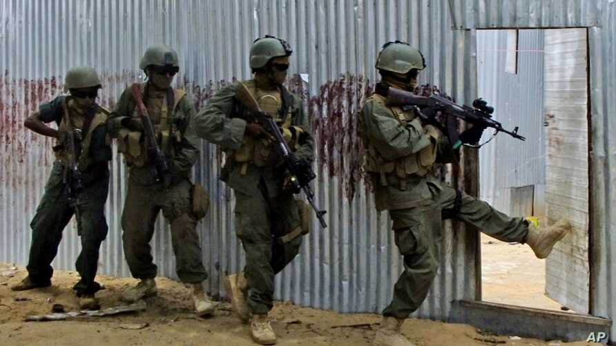 Masked Somali national army (SNA) soldiers search through homes for al-Shabaab fighters, during an operation in Ealsha Biyaha, Somalia, Saturday, June, 2, 2012.