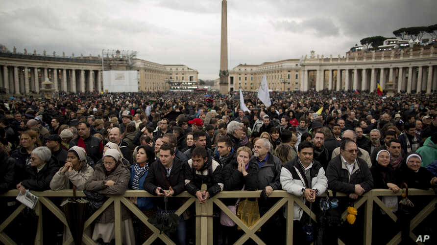 Visitors wait for the chimney smoke in St. Peter's Square during the second day of the conclave to elect a new pope, at the Vatican, Mar. 13, 2013.