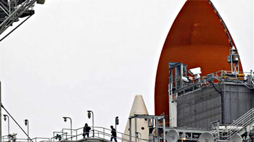 NASA workers walk near the external tank, rear, of the space shuttle Discovery at the Kennedy Space Center in Cape Canaveral, Florida, February 23, 2011