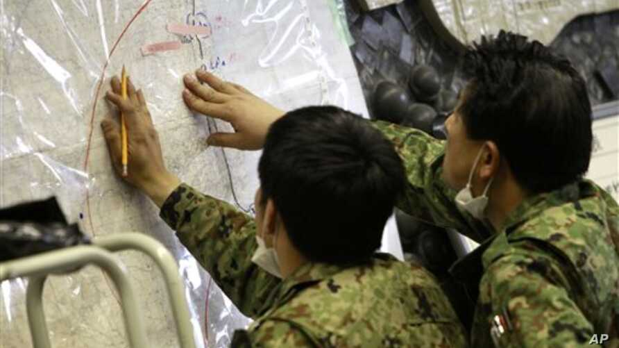 Japan's Defense Ministry officials plot possibly radioactive affected areas on a map at the emergency rescue headquarters monitoring leaked radiation from the Fukushima nuclear facilities, Fukushima city, Fukushima prefecture, Japan, March 16, 2011