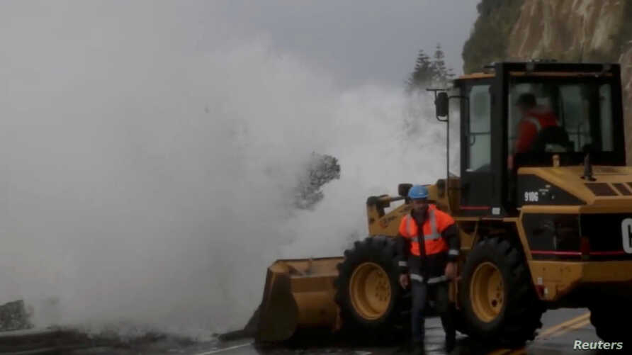 A wave hits heavy machinery as emergency personnel work on a flooded road in Nelson, after the downgraded tropical cyclone Fehi brought heavy rain in New Zealand, Feb. 1, 2018.