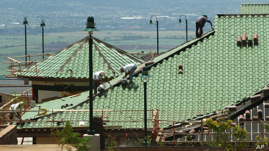 FILE - Workers install roof shingles on a building in Pukalani, Hawaii, July, 12, 2002.