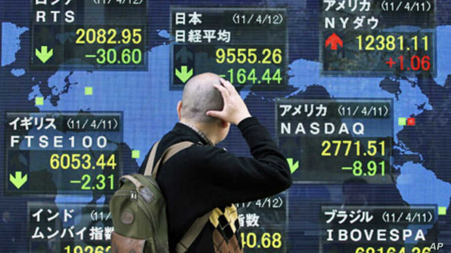 A man looks at the closing price of Japan's Nikkei share average (top C) displayed along with major indexes outside a brokerage in Tokyo, April 12, 2011