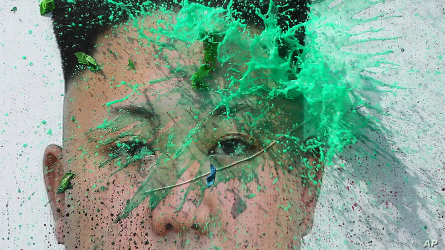 A balloon thrown by a North Korean defector containing a colored liquid bursts on a portrait of North Korean leader Kim Jong Un during a rally protesting North Korea, March 30, 2016, in Seoul, South Korea.